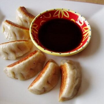 pan-fried dumplings fanned out around a red and yellow bowl of dipping sauce