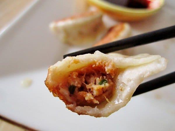 A closeup of a half-eaten dumpling between two chopsticks