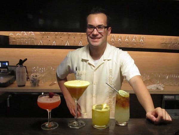 a man standing behind a bar lined with four different cocktails