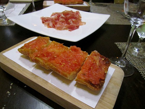 crispy pieces of bread rubbed with tomato on a wooden board