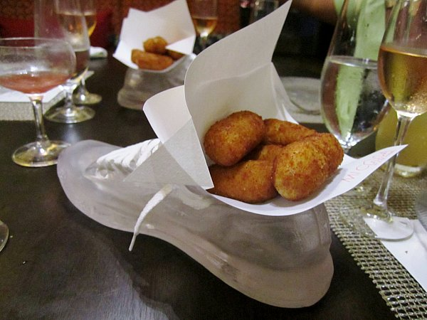 a sneaker shaped serving dish filled with fried croquettes