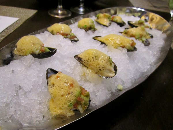 mussels on the half shell topped with foam on a bed of crushed ice