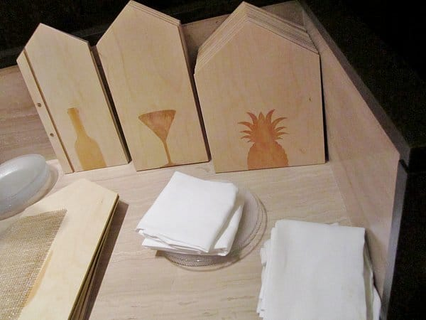 wooden menu covers shaped like houses with burnished images on them