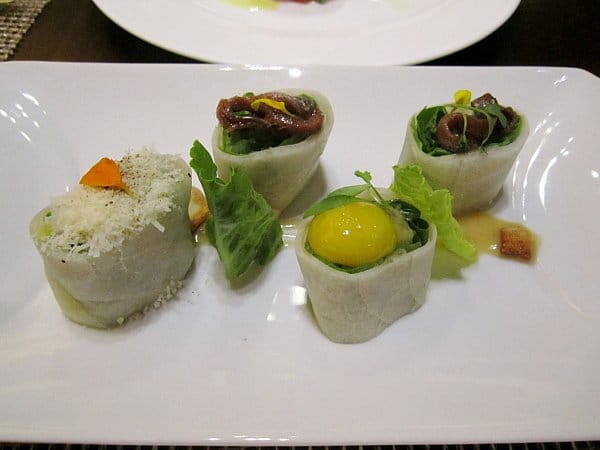 rolls topped with anchovies and egg yolk on a white plate