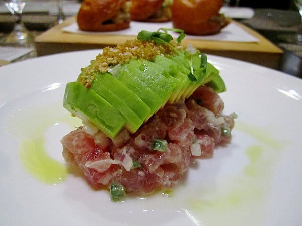 chopped raw tuna topped with sliced avocado on a white plate