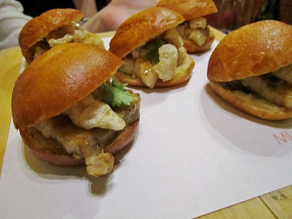small buns filled with pork belly and chicharróns on a white surface
