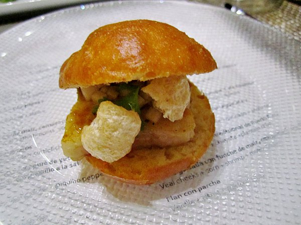 a small bun filled with pork belly and chicharróns