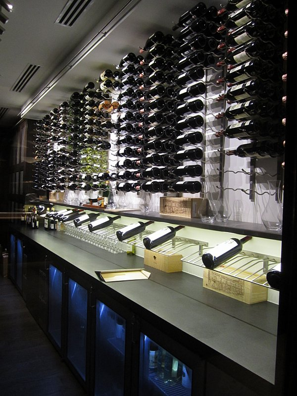 a wall covered with rows of bottles of wine