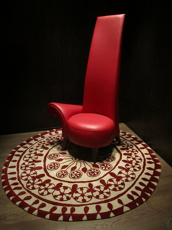 a very tall red chair on a round red and white rug