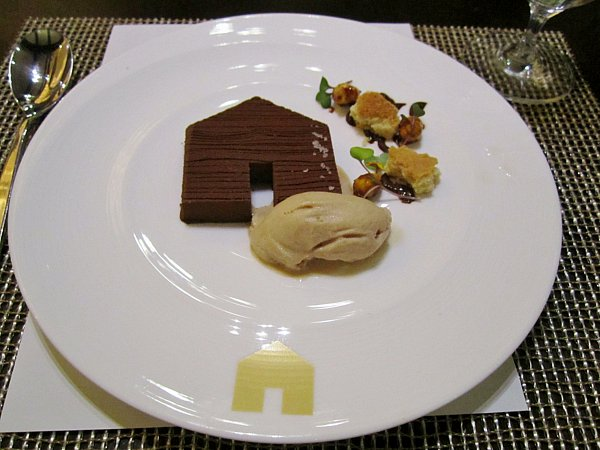 a chocolate house shaped dessert with ice cream on a white plate