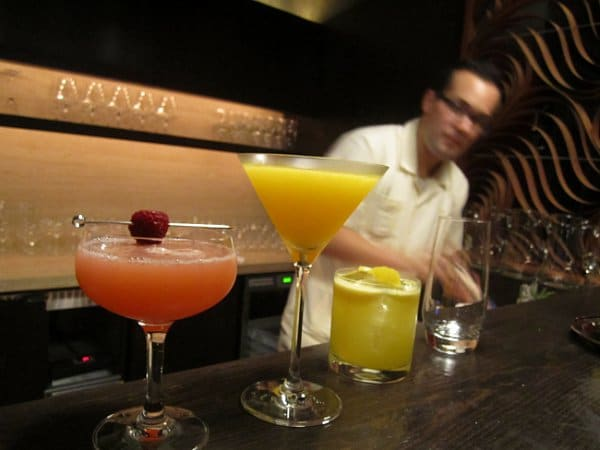 a variety of drinks lining a bar in a restaurant