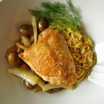 overhead view of a crispy chicken thigh with olives and rice in a white dish