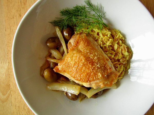 wide view of a chicken thigh with olives, fennel and rice in a round white dish