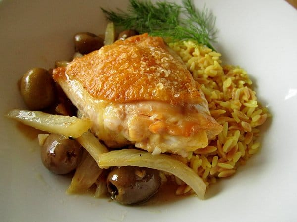 closeup of a crispy chicken thigh with olives, fennel, and rice pilaf in a white dish