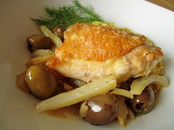 closeup of cooked strips of fennel and green olives topped with a crispy chicken thigh