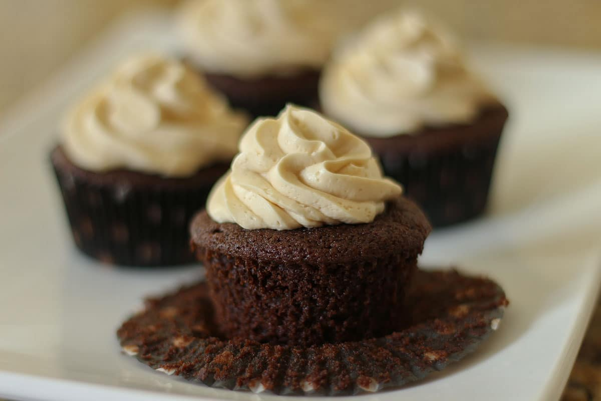 Frosted chocolate Guinness cupcakes on a white plate with the paper liner peeled off of one.