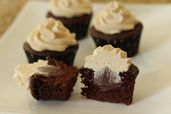 Chocolate cupcakes with Baileys Irish Cream buttercream frosting piped on top, with polka dot cupcake liners on a white plate. One of the cupcakes is cut in half to show a chocolate filling on the inside.