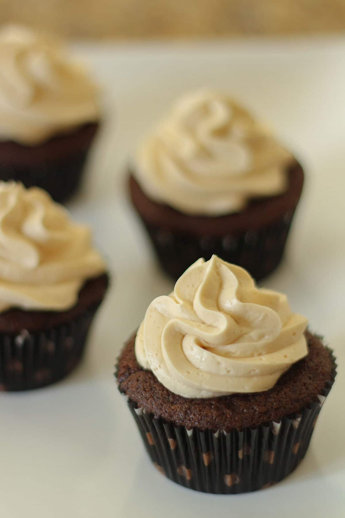 Closeup of frosted chocolate cupcakes with polka dot liners on a white plate.