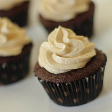 Frosted chocolate cupcakes with polka dot liners on a white plate.
