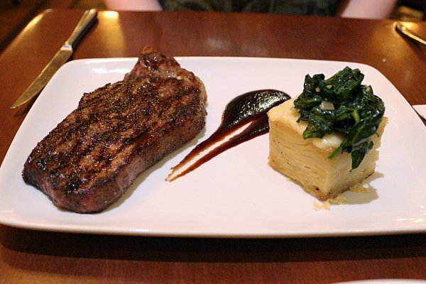 a cooked steak on a white plate next to a square shaped potato gratin