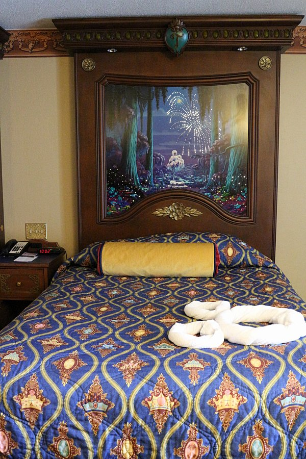 A double bed with a dark blue bedspread in a hotel room