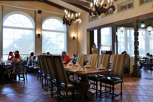 A restaurant dining room with tables, chairs, and large windows