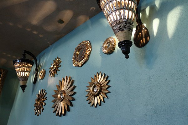 round metal decorations and lights on a blue wall