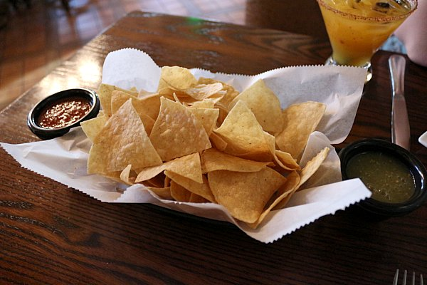 a basket of tortilla chips with cups of red and green salsa on either side