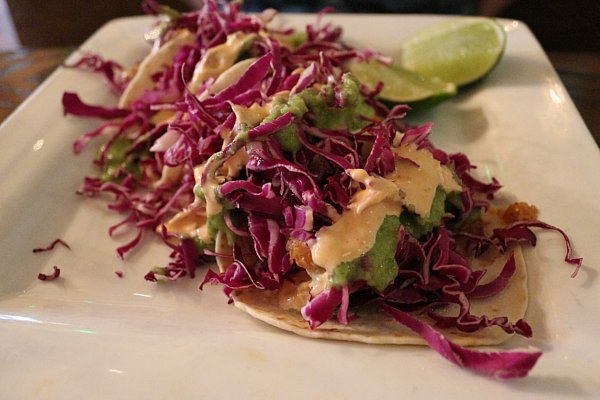 A plate of tacos with lots of red cabbage on top