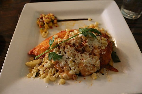fish served with corn on a white plate