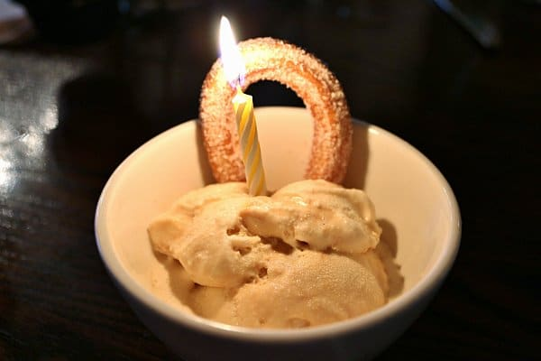 a bowl of ice cream with a churro and yellow birthday candle stuck into the top