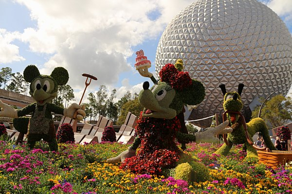 a topiary of Mickey, Minnie, and Pluto in front of Spaceship Earth at Epcot