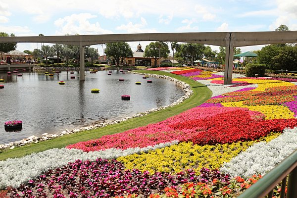 A bridge over a body of water surrounded by colorful gardens