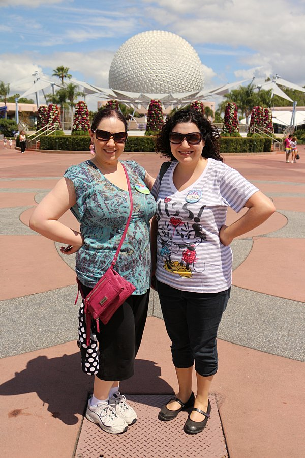 two women posing in front of Spaceship Earth at Epcot
