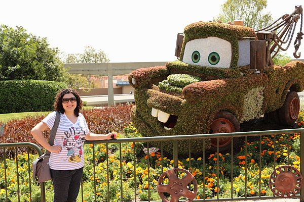 A woman posing next to a topiary that looks like Mater from Cars