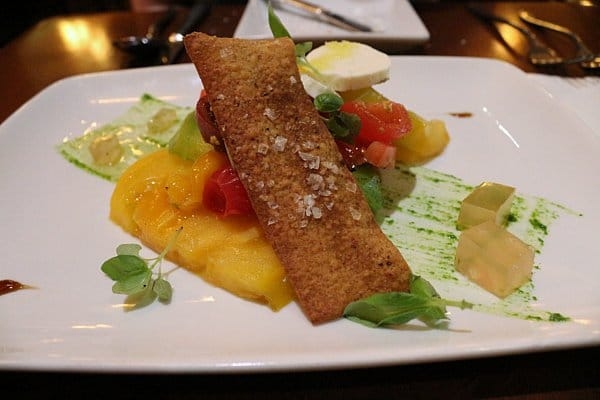 a salad with yellow heirloom tomatoes and mozzarella on a white plate