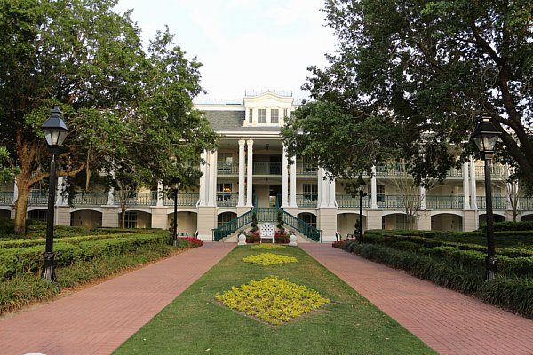 A plantation style building with a garden in front