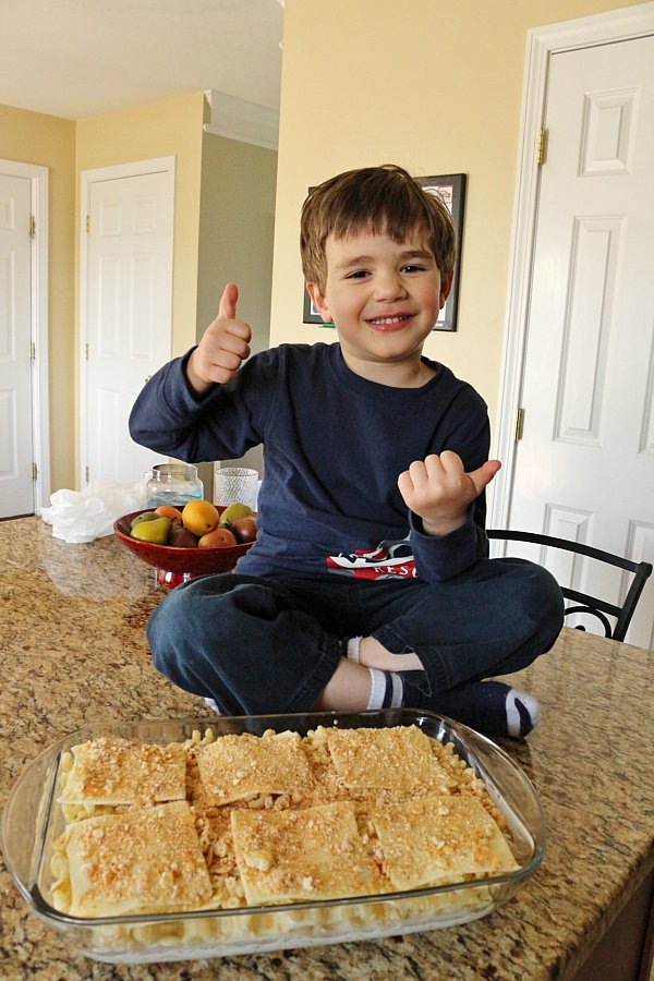 A little boy sitting on a counter giving two thumbs up