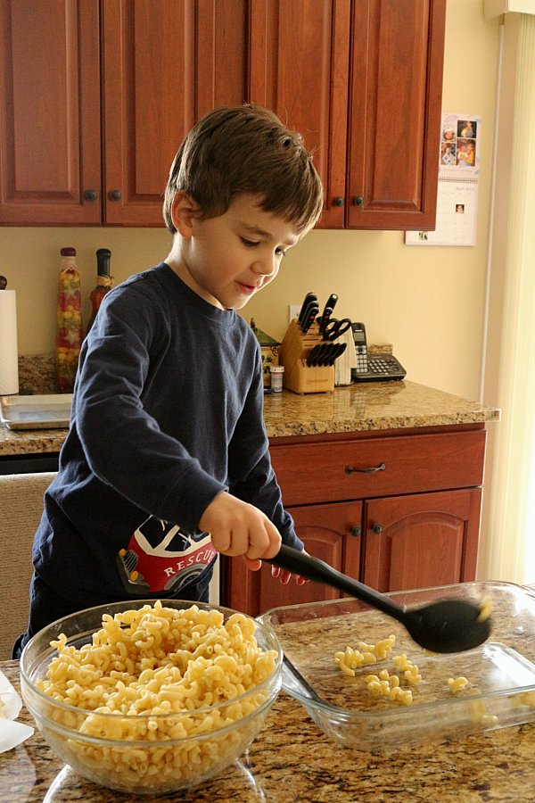 A young boy scooping cooked macaroni into a glass baking dish