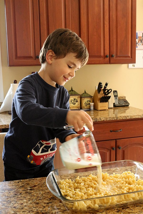 A boy pouring milk out of a measuring cup into a glass baking dish