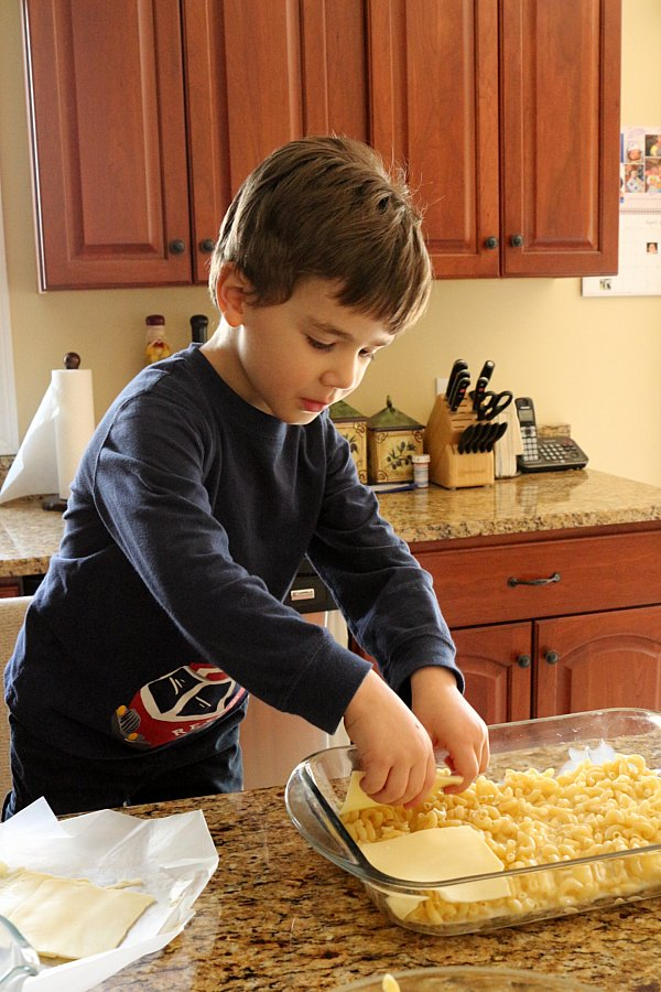 A boy arranging slices of cheese into a glass baking dish