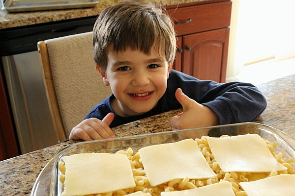 a boy giving a thumbs up behind a casserole he is helping to prepare