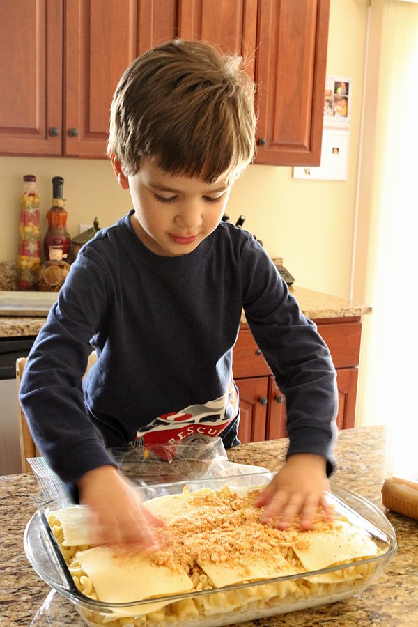A young boy spreading crushed cracker crumbs over a casserole dish