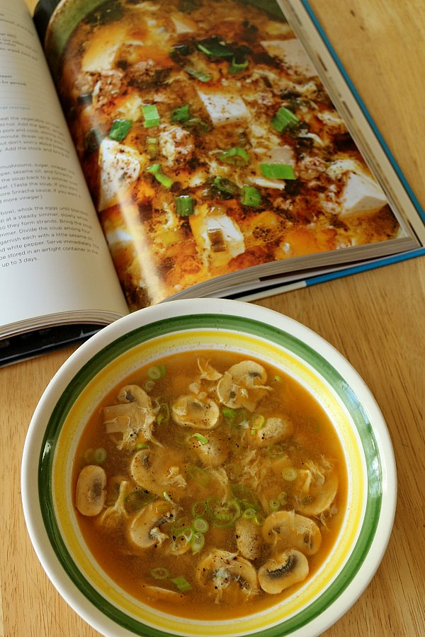 A bowl of soup sitting on a table next to an open cookbook