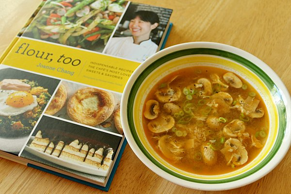 A bowl of soup next to a cookbook on a wood table