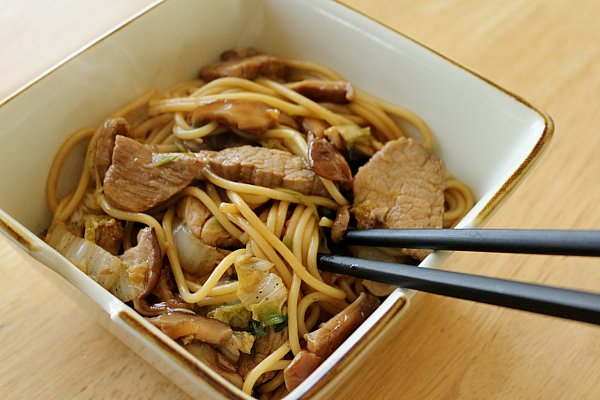 lo mein noodles with sliced pork and mushrooms in a square bowl with black chopsticks