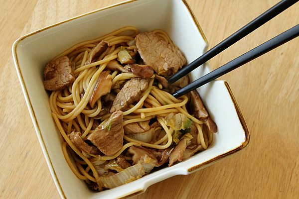 overhead view of a square bowl filled with Asian noodles with sliced pork, mushrooms, and chopsticks