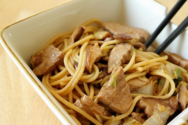 a closeup of pork lo mein noodles in a square bowl with black chopsticks
