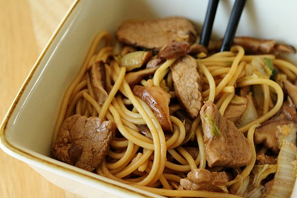 closeup of a square bowl filled with noodles, sliced pork, and mushrooms