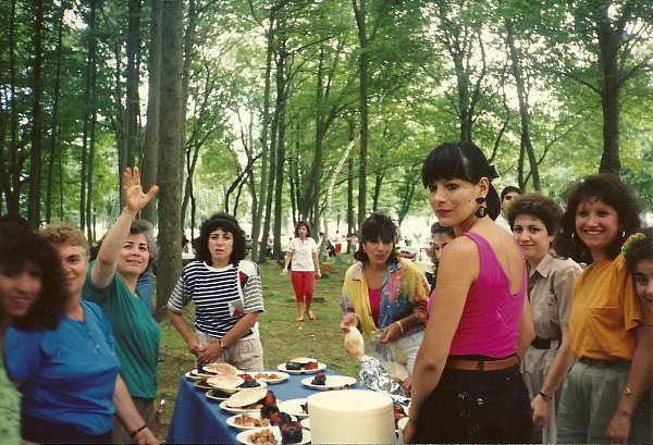 An old photo of a group of Armenian women filling plates of grilled food at a picnic